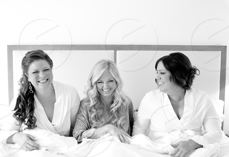 3 woman sitting on bed wearing their own robe photo