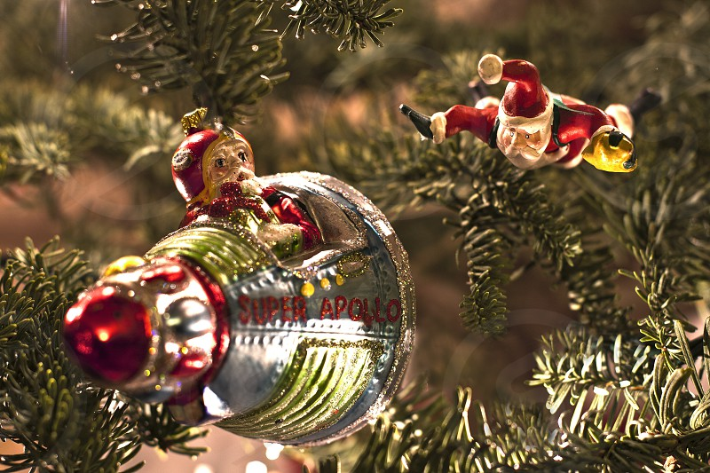 Close-up of glass Christmas ornaments (Santa flying a space capsule and flying santa) hanging on a Christmas tree. (blurred background) photo