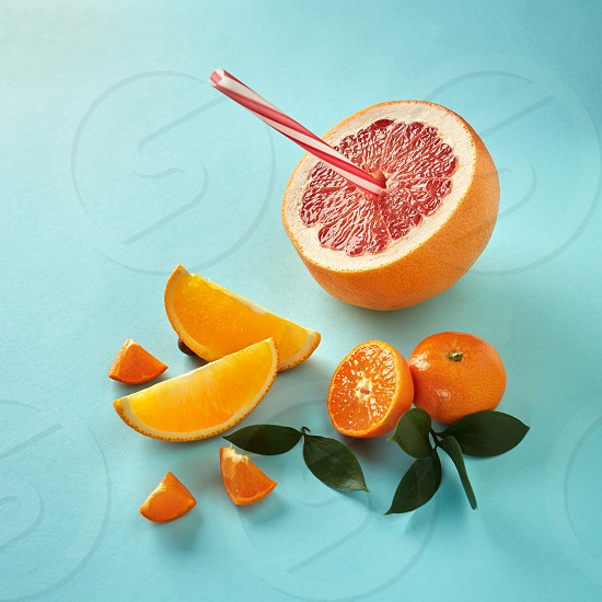 Tropical exotic citrus fruits half a grapefruit tangerines orange slices with a plastic straw for juice on a blue paper background photo