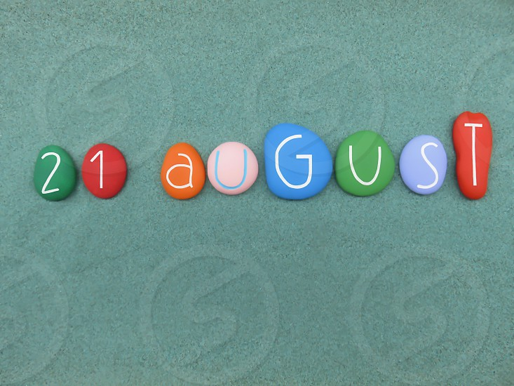 21 August calendar date composed with multi colored stones over green sand                          photo