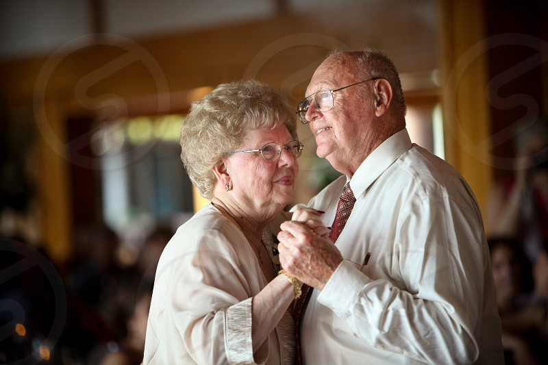 A happy elderly couple dressed in formal wear dance indoors. photo