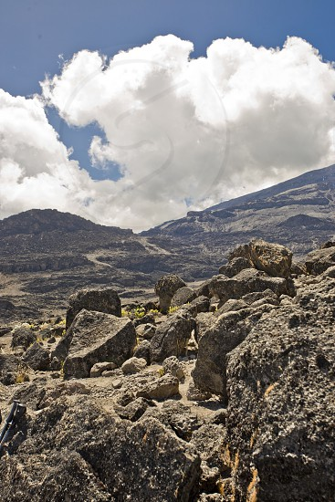 Mt. Kilimanjaro and the rough terrain and rocks with clouds overhead. photo