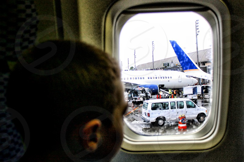Boy lookout an airplane window just before the plane leaves the gate. photo