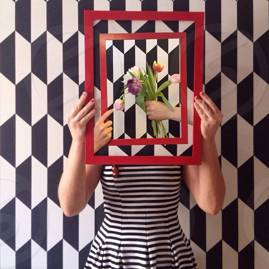 woman in black white striped dress holding up red framed photo of hand holding flowers over her face photo