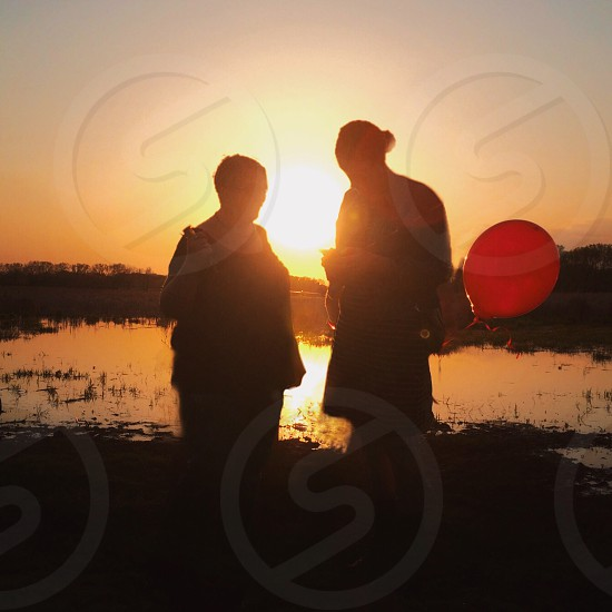 sunset behind 2 women with red balloon photo