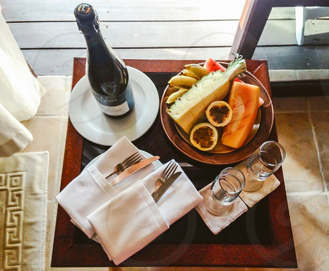 Champagne breakfast tropical fruit fresh banana pineapple watermelon passion fruit papaya silver service champagne glasses photo