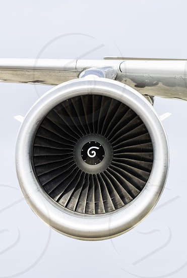 Jet engine on the airplane wing. Close-up frontal view of the jet engine and sky on the background. Air transport conception. photo