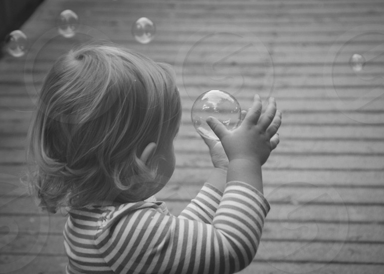 Child catching a bubble photo