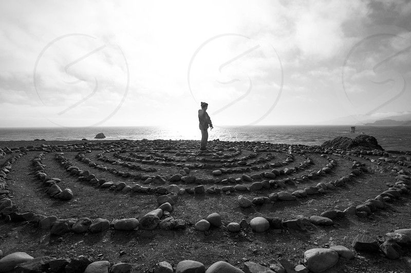 grayscale photography of woman standing on the center of circle form stones photo