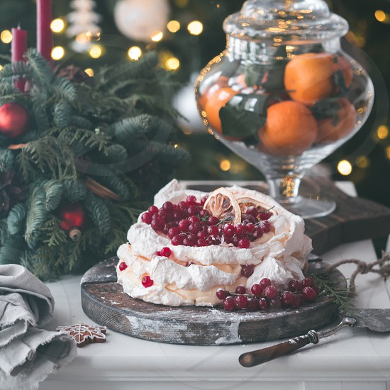 Meringue cake Pavlova with fresh red currant and whipped cream on fir christmas tree background. Mood and Atmospheric photo for winter holidays. New Zealand Australian dessert pavlova. Copy space photo