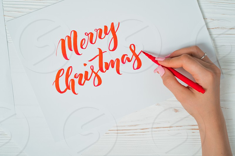 Merry Christmas congratulations. Calligrapher writes with red ink on white card. Calligraphy. Ornament font. The art of lettering. Graphic design handwriting creation concept. photo