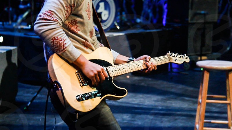 man performing on stage using guitar photo