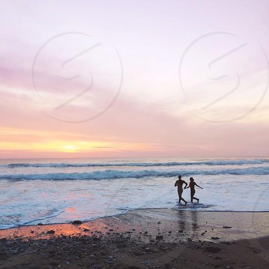 couple dashing to the ocean photo