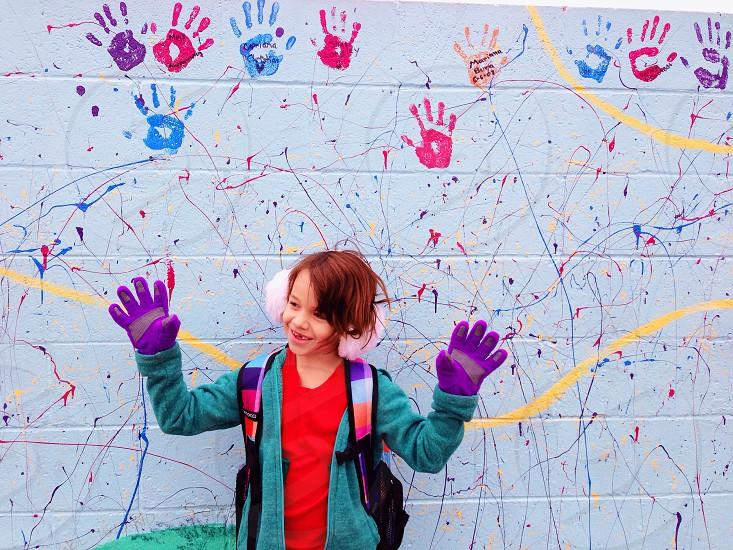 girl wearing a blue long sleeve jacket beside wall photo