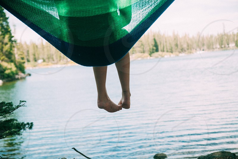 person sitting on blue mesh hammock by water during daytime photo