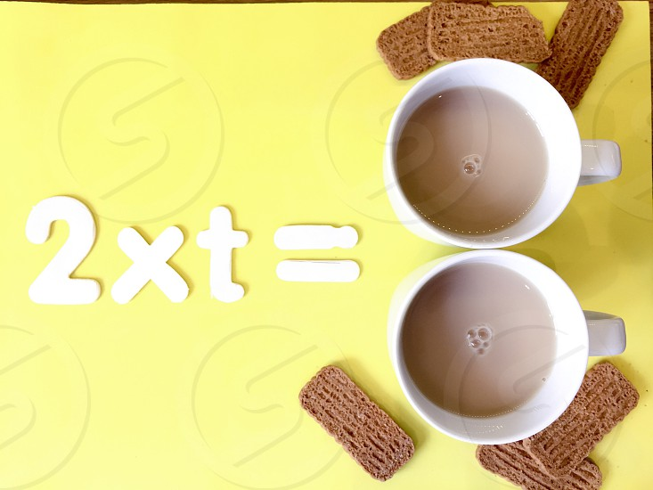Concept.   Two x tea =  and an image of two cups of tea and biscuits on a yellow background photo