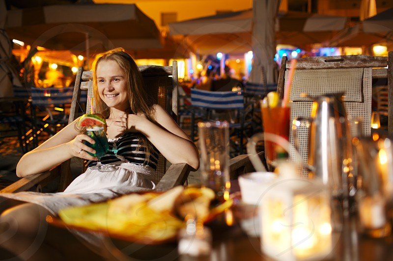 Smiling vivacious beautiful young woman sitting drinking at a counter in a cafeteria or pub in an indoor illuminated mall photo