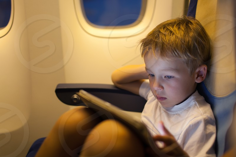 Little boy sitting in the plane and playing on touch pad. Traveling by air photo