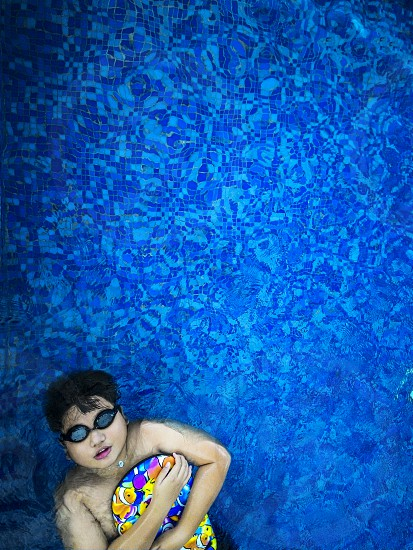 Kid floating on water in swimming pool photo