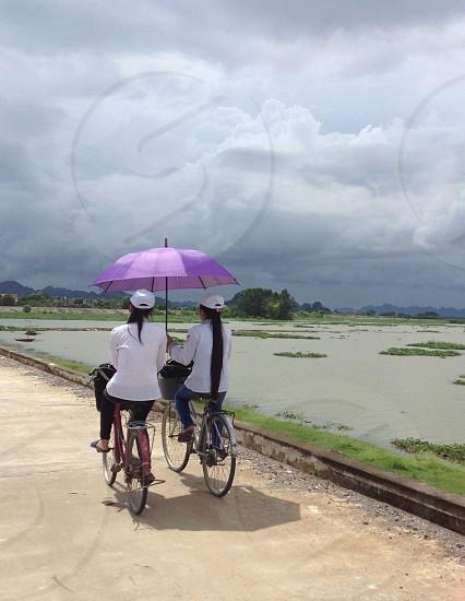 best friends on bike sharing an umbrella photo