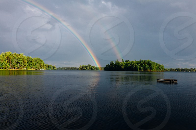 green island with rainbow under grey and cloudy sky at daytime photo
