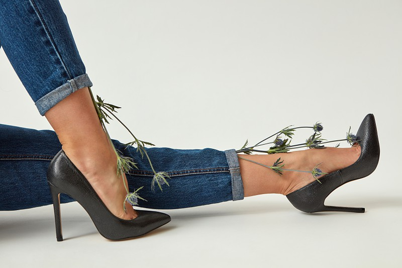 Beautiful female legs in jeans decorated blue flowers eryngium on a white background. Mother's Day Valentine's Day photo