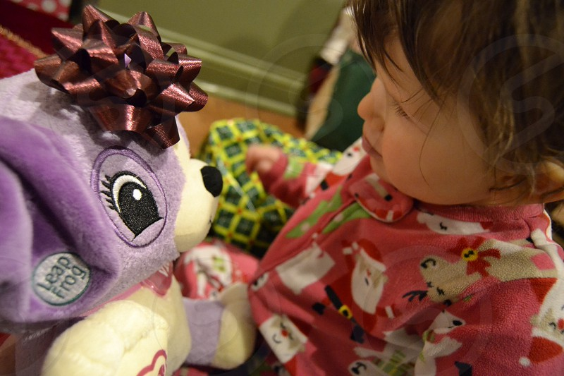 child in santa and reindeer print pajamas looking at purple leap frog plush toy photo