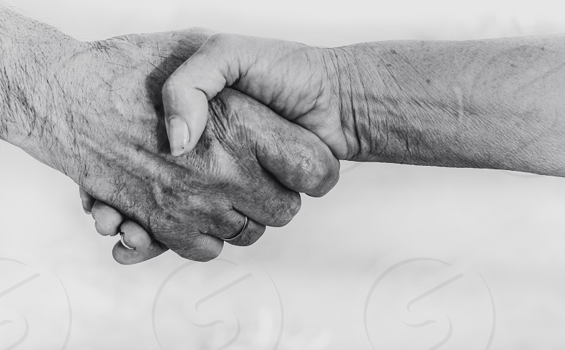 Handshake of senior man and woman on white background monochrome effect - greeting dealing merger and a acquisition concepts photo