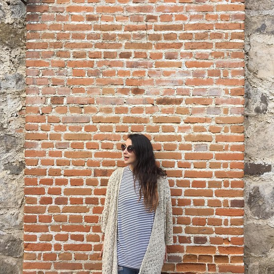 woman wearing cream knit cardigan standing in front of brick wall photo