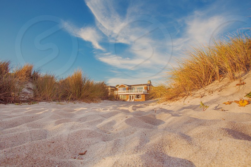 worm's eye view of 2 story house surrounded by grass and sand under cloudy sky photo
