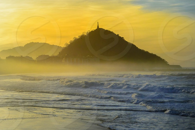 mountain near sea during sunrise photo