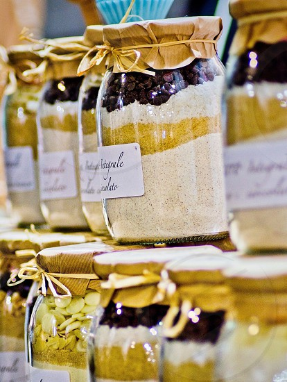 glass jars with white powders and berries on display photo