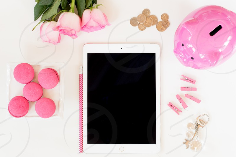A feminine lay flat desktop with pretty pink details of a piggy bank tablet macarons crystal key chain with an old fashioned key paper clips roses and coins.  Room for copy space on the tablet. photo