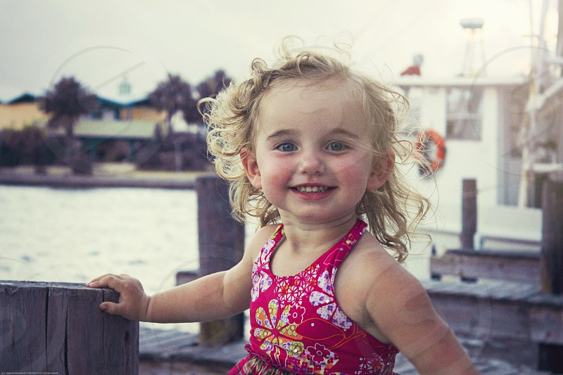 Little girl standing on the boat dock smiling.  photo