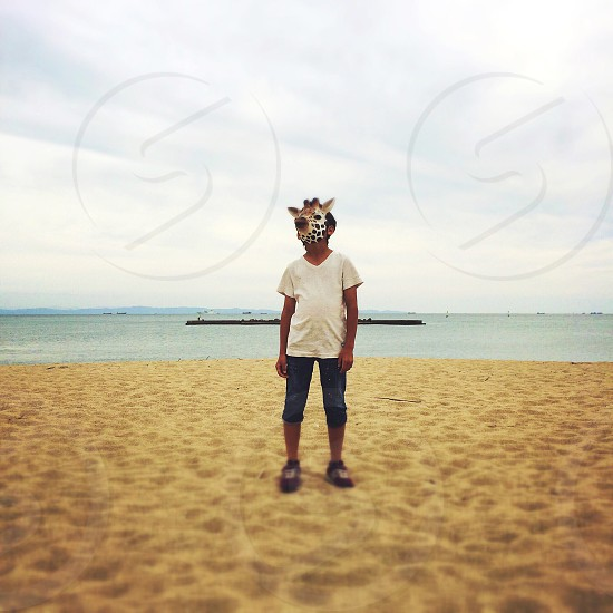 man in white v neck t shirt with giraffe mask standing on the seahore photo