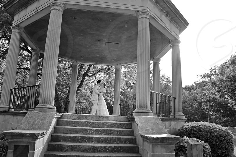 newly wed kissing under gazebo photo