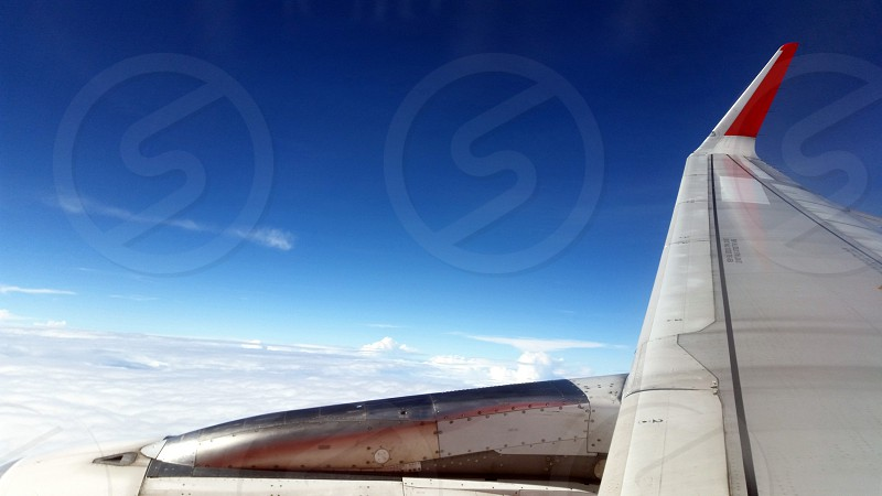 view of gray plane wing from window under blue sunny sky during daytime photo