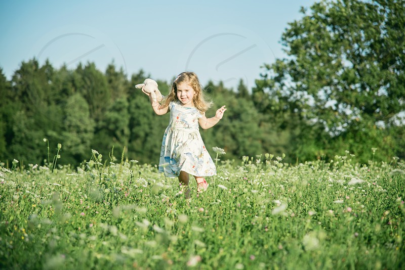 Young happy girl running through meadow field and smiling. photo