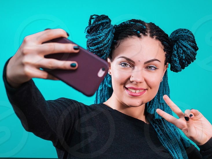 Portrait of young attractive hipster woman with dyed colorful african braids making selfie photo on smartphone isolated on turquoise background. Exotic girl smiling. photo