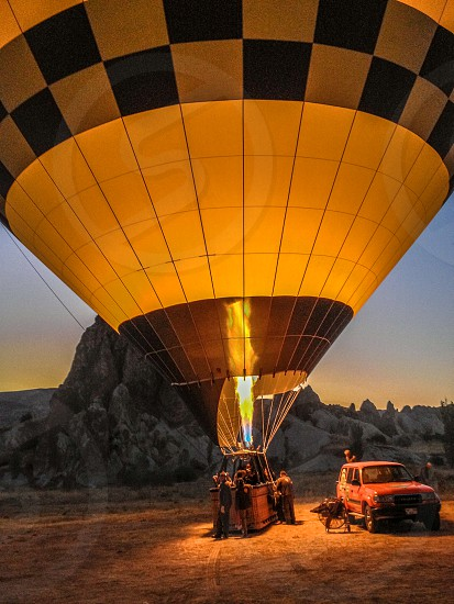 people assembling a brown and black hot air balloon near a red pickup truck photo