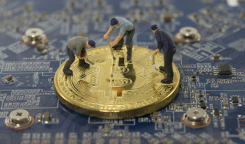 little world figures mining bitcoins on electronic print plate photo