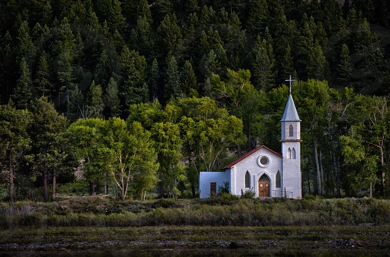 A little white church built by the base of a mountain in Colorado photo