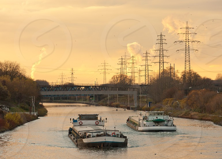 Inland waterway vessels on a busy channel in industrial area near a bridge under the warm glow of an evening sunset photo