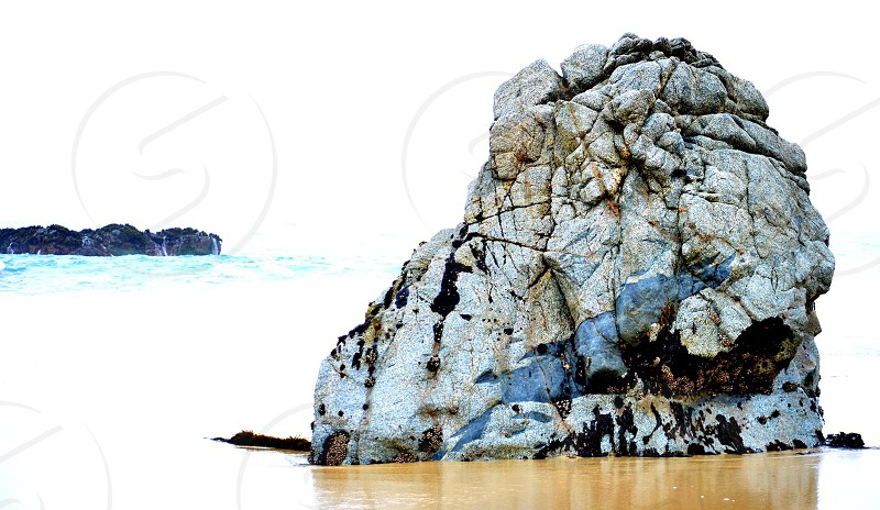 rock formation in the middle of sea photo