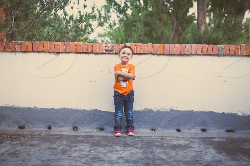 boy in orange crew neck t shirt and blue denim jeans standing beside beige and grey painted concrete wall photo