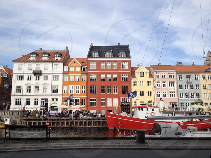 concrete houses near river with docked red and white boat photo