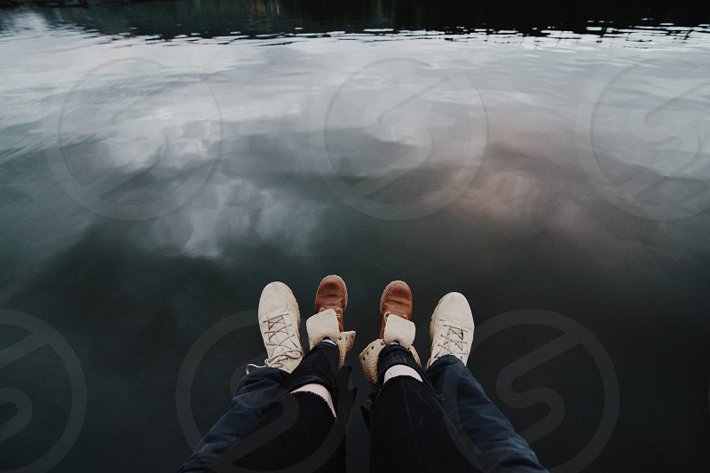 two people wearing black pants and two pairs of black and brown shoes sitting over the water during daytime photo