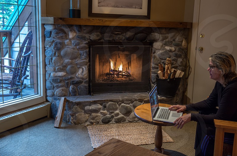 Creative working by fireplace in a cabin photo