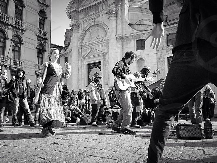 man playing guitar beside woman dancing photo