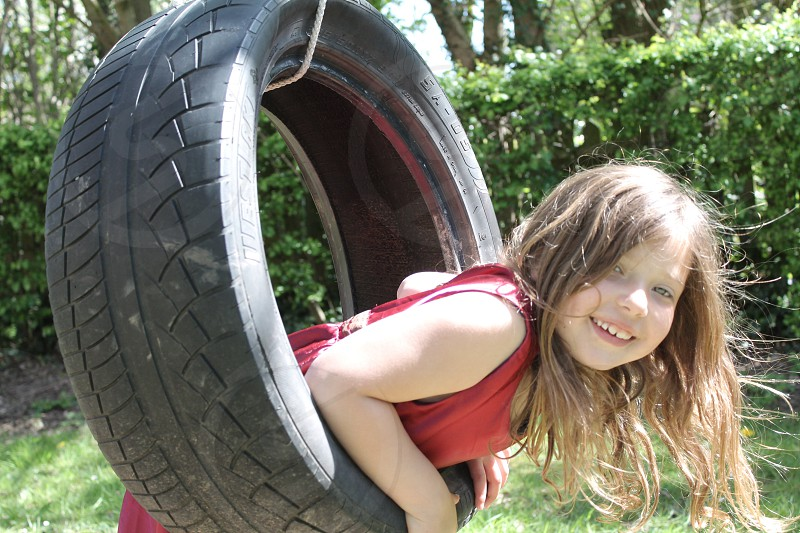 girls riding rubber tire swing photo
